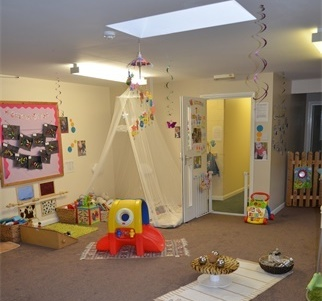 Baby room in Little Fingers Day Nursery is decorated in calming colours, and babies' artwork is displayed on the walls